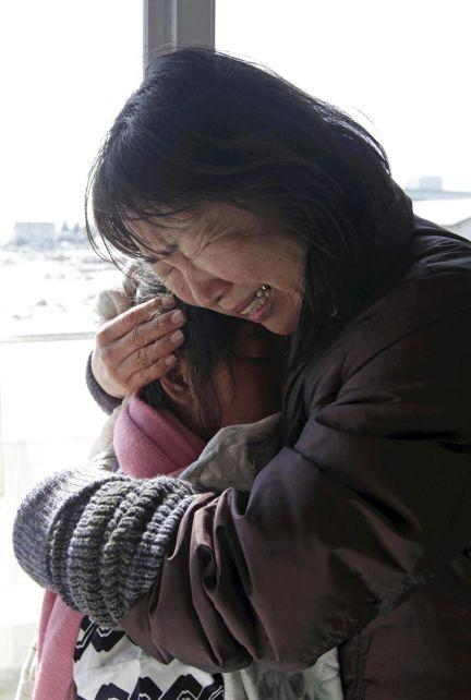 El abrazo desesperado de una mujer a su nieta en Natori (Fukushima) retrata bien el drama de los 600.000 evacuados. Foto: AFP