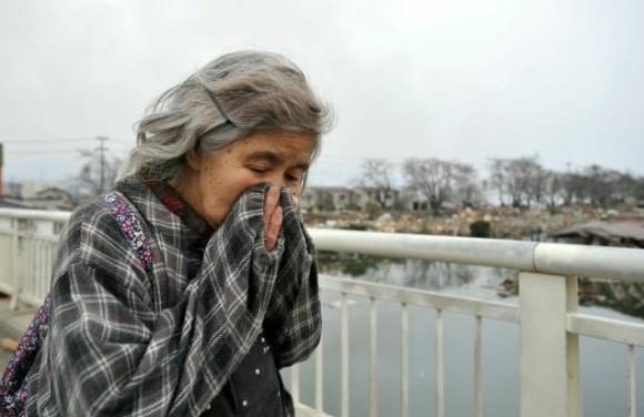Una mujer anciana se cubre el rostro para ocultar su sufrimiento al comprobar que su casa es una de las que fueron arrasadas por el terremoto y posterior tsunami que asolÛ el pasado viernes el noreste de JapÛn, en Kesennuma, en la provincia de Miyagi, a unos 300 km de Tokio (JapÛn), hoy, martes, 15 de marzo de 2011. Las autoridades japoneses aumentaron hoy a 2.414 los fallecidos y a 3.118 los desaparecidos por el terremoto y posterior tsunami del viernes en el noreste del paÌs, de acuerdo al ˙ltimo recuento de la PolicÌa. Sin embargo, se cree que la cifra final de vÌctimas puede ser mucho mayor. Por otro lado, las autoridades adviertieron de un posible aumento de la radiaciÛn tras un incendio y una explosiÛn en la central nuclear de Fukushima, en torno a la cual se ha declarado una zona de exclusiÛn aÈrea de 30 kilÛmetros. EFE/KIMIMASA MAYAMA