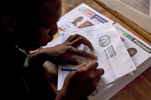 Un hombre con una boleta electoral de los controles en un colegio. Segunda vuelta presidencial en Puerto Príncipe, Haití, Domingo, 20 de marzo 2011 - Ap Agencia
