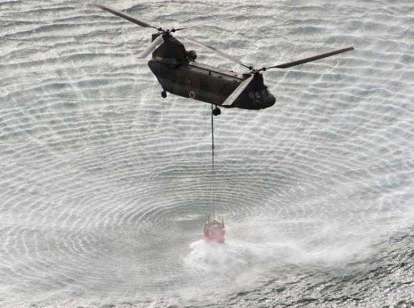 El Helicóptero de la Fuerza Aérea de Japón lleva agua de mar para verter sobre sobre el reactor de Fukushima. Foto: AFP