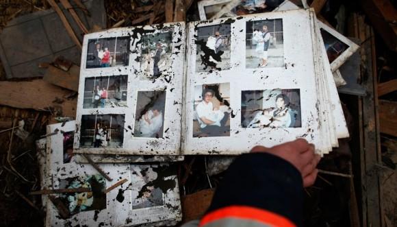 Un bombero mira un álbum familiar, localizado entre las ruinas de Otsuchi, en la prefactura de Iwate. Foto: Reuters