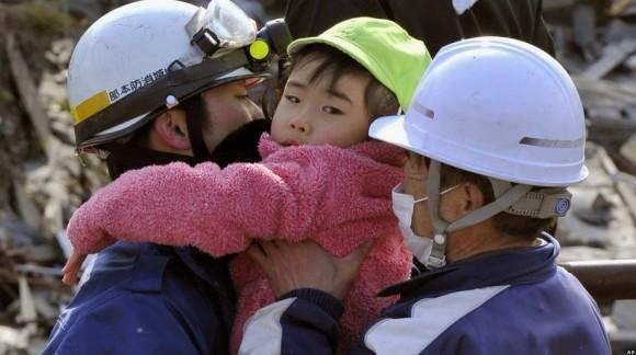 Una niña pequeña es atendida por trabajadores de auxilio, tras ser rescatada de un edificio en Kesensuma, en el noreste de Japón, un día después de que un devastador maremoto azotara la costa noreste del país. (AP Photo/Kyodo News)