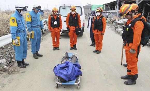 Miembros de los servicios de rescate surcoreanos presentan sus respetos ante el cadáver de una víctima del terremoto en Sendai, en la provincia de Miayagi. Foto: EFE