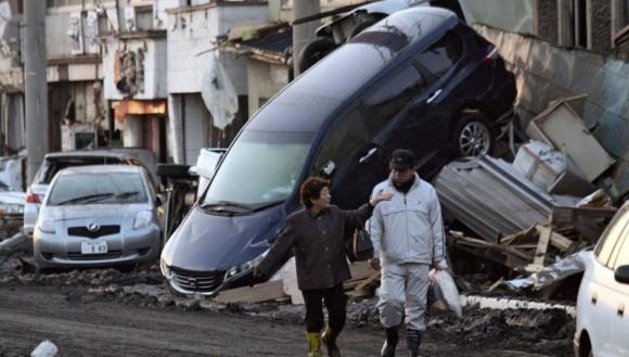 Una pareja pasa frente a coches dañados por el terremoto y el tsunami que azotaron la región de Iwate.  Foto: AFP