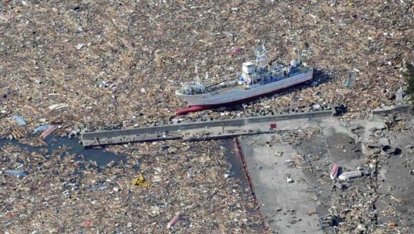 Un barco pesquero navega entre escombros cerca de la ciudad de Kamaishi, en Iwate. Foto: AFP