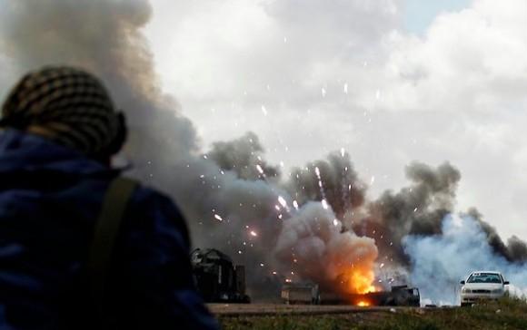 Unas personas observan las llamas de un vehículo junto a la carretera, después del impacto de una bomba. Foto: Rueters
