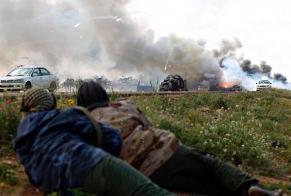 Unas personas observan las llamas de un vehículo junto a la carretera, después del impacto de una bomba.