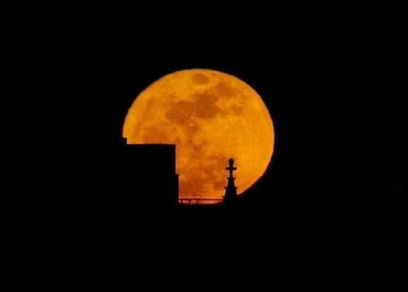 """La luna llena se eleva sobre los tejados del lado este de Manhattan, Nueva York. La luna llena coincide con sus mayor acercamiento a la Tierra de 356,575 kilometros, por lo que la llamada   """"Super Luna"""" se ve un poco más grande de lo normal."""