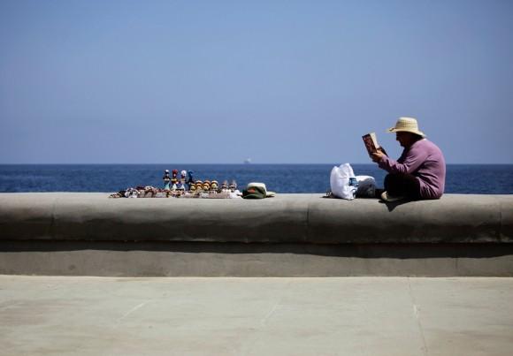 A mujer con una licencia privada para vender recuerdos lee un libro mientras espera para los clientes en el bulevar marítimo de La Habana