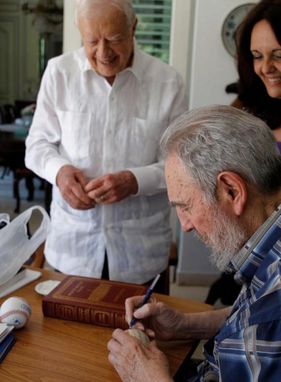 Fidel Castro (derecha) firmas una pelota de béisbol para el ex presidente de EE.UU. Jimmy Carter durante una reunión en La Habana. (Alex Castro / AFP / Getty Images)