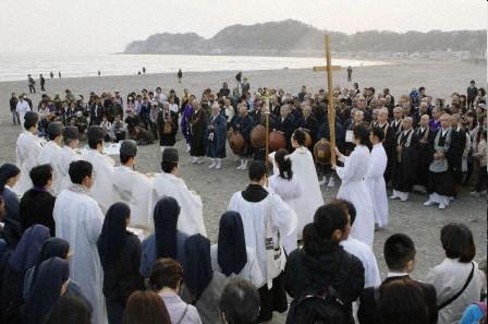 """Un grupo de sintoístas, budistas y cristianos oran en una ceremonia conjunta """"para apaciguar al mar"""" en la playa de Yuigahama (Kamakura, prefectura de Kanagawa) el día 11 de abril. Foto: Agencia Kyodo."""