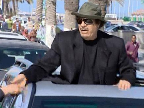 Imagen tomada de la cadena de televisión Al Arabiya que se observa al líder libio Muammar Gaddafi mientras saluda a varios peatones hoy, jueves 14 de abril de 2011, desde la claraboya de un vehículo en Trípoli (Libia).