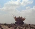 En esta imagen tomada por televisión se observa una nube de tierra trals la explosión de un misil afuera del uerto estratégico de Brega, en Libia, el jueves 7 de abril del 2011. Un ataque aéreo de la OTAN destruyo una caravana de vehículos rebeldes el jueves, matando a por lo menos cinco combatientes y generando un gran enojo entre las fuerzas antigubernamentales debido a la segunda misión fallida en una semana de la alizanza militar extranjera. (Foto AP/Consejo de Transición Nacional de Libia, AP Television News)