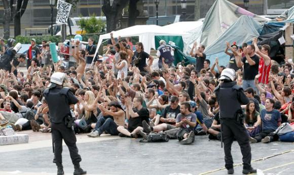 """Los Mossos d'Esquadra han desalojado hoy la plaza de Cataluña de Barcelona y han cargado contra los """"indignados"""" que intentaban evitar la salida del lugar de los camiones de limpieza cargados con los enseres y herramientas de los acampados. Foto: EFE/Albert Olivé"""
