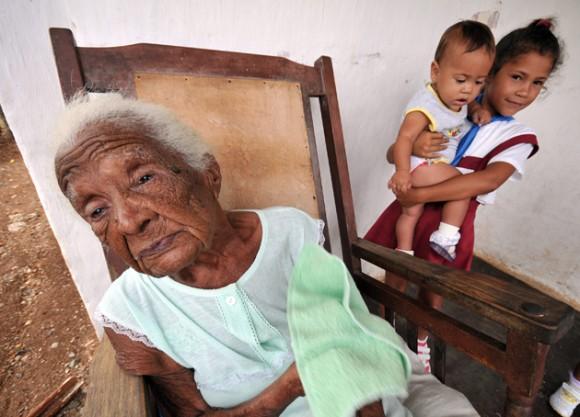 La cubana Juana Bautista de la Candelaria posa con sus tataranietas Yuleinnis, de 7 meses, y Yelennis de siete años. Foto: Alejandro Ernesto, EFE