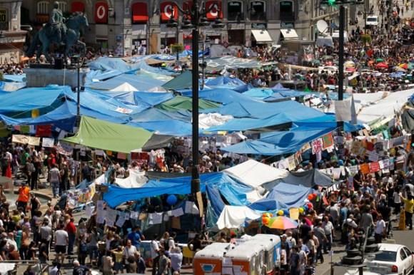 Foto: Miles de personas que continúan concentradas en la madrileña la Puerta del Sol han acordado hoy mantener las concentraciones al menos durante una semana más, hasta el próximo domingo a las 12 del mediodía, para articular mejor el movimiento y poder conseguir así un cambio social. EFE/Chema Moya