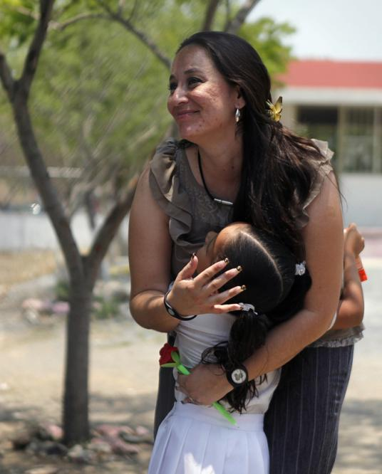 La maestra mexicana Martha Rivera Alanis recibe un cariñoso abrazo de una de sus alumnas. Foto: Tomás Bravo (Reuters).