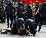 Los mossos reducen a un indignado durante el desalojo de la Plaza Catalunya de Barcelona.