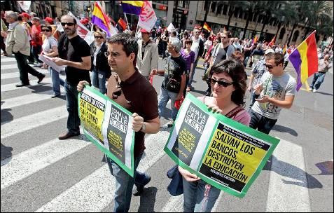 Un hombre y una mujer portan carteles aludiendo a la situación de crisis en la manifestación en Valencia del Día del Trabajo.- EFE/Manuel Bruque