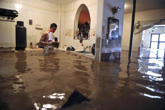 Un hombre recoge sus pertenencias dentro de su casa inundada en Cali, Colombia, el 22 de abril. | Foto: Luis Robayo / AFP