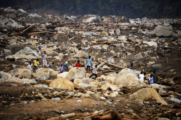 Pobladores se reúnen en el lugar de un devastador deslizamiento de tierra en Nakau, Tailandia, después de las lluvias torrenciales del 01 de abril. Graves inundaciones en el sur de Tailandia han dejado 25 muertos y provocado que miles tengan que ser evacuados, después de que aldeas enteras fueran devoradas por las crecientes aguas. | Foto: Madaree Tohlala / AFP
