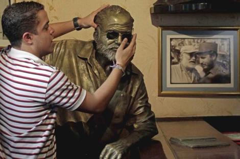 Un turista pone sus gafas sobre una estatua de Hemingway en La Habana. Foto: AP