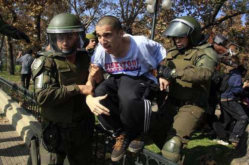 Un estudiante universitario que participaba en las protestas en Santiago es arrestado por miembros de la policía militarizada de Carabineros. Foto: Reuters