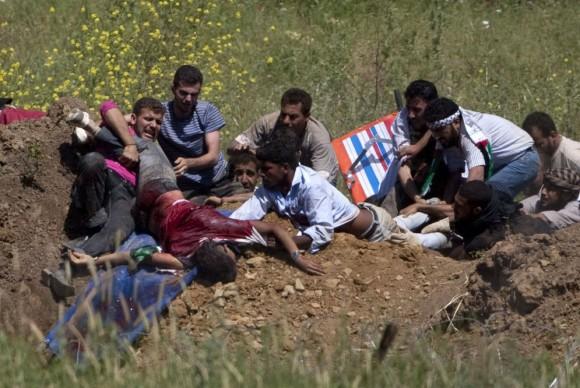 Un grupo de manifestantes palestinos trata de ayudar a un compañero herido por disparos de soldados israelíes cuando trataban de cruzar la frontera desde Siria. Foto: AFP