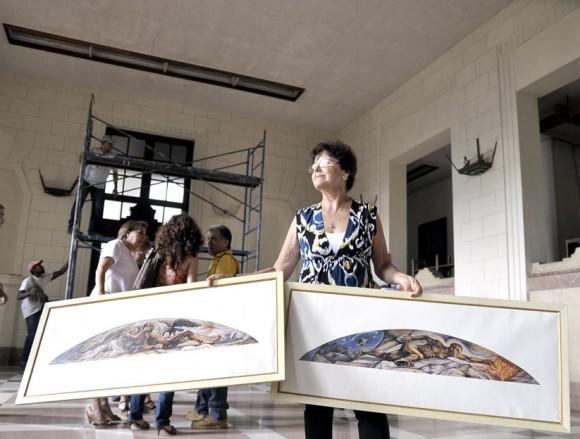 Mariana Ravenet muestra dos lienzografías con las pinturas de los murales de su padre. Foto Kaloian