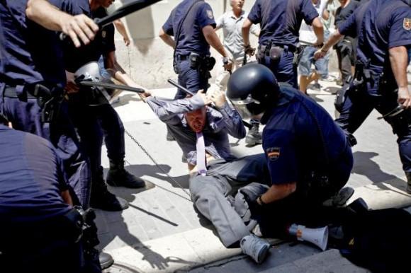 """Agentes de la Policia Nacional cargaron hoy contra los """"indignados"""" del movimiento 15-M que protestaban ante Les Corts Valencianes durante la constitución de las mismas, y detuvieron a cinco personas del grupo por desorden público, atentado a la autoridad y causar lesiones a algunos agentes, después de que propinaran puñetazos y lanzaran botellas de agua durante la carga policial. EFE/Biel Aliño"""