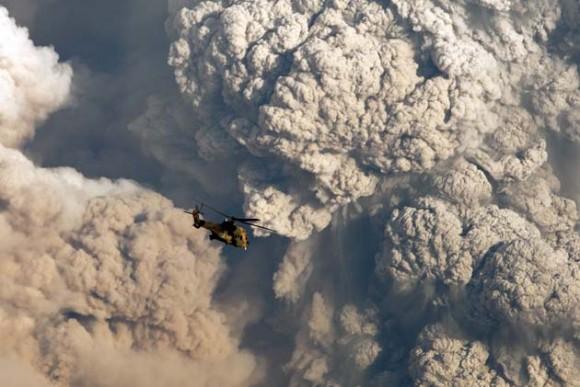 Un helicóptero militar vuela hoy, domingo 5 de junio de 2011, frente la columna de humo provocada por una explosión en el complejo volcánico Puyehue - Cordón Caulle en Riñinahue (Chile). Las autoridades chilenas detectaron una disminución en la actividad sísmica del lugar, del que emana una nube de humo y cenizas que hasta ahora se ha dirigido hacia Argentina y que en las próximas horas puede afectar con más fuerza a territorio chileno. EFE/Ian Salas