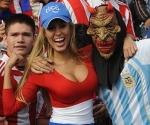 Una fanática de Paraguay alienta a su equipo junto a un simpatizante de la selección argentina en las tribunas del estadio cordobés