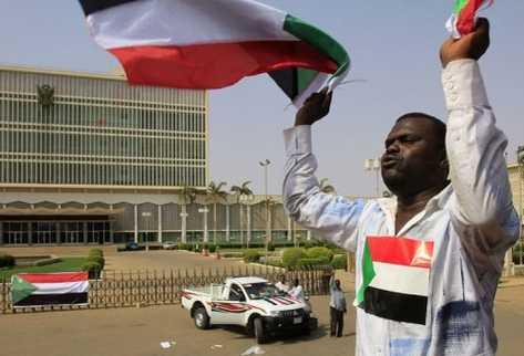 Un sudanés agita unas banderas en Jartum horas antes de la proclamación oficial de la independencia de Sudán del Sur