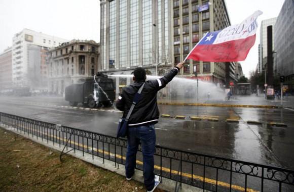 Un manifestante ondea una bandera chilena frente a un vehiculo antidisturbios hoy, miércoles 24 de agosto de 2011, durante una protesta en Santiago de Chile en el marco de la primera jornada de paro nacional de dos días convocado por la Central Unitaria de Trabajadores (CUT). Una normalidad relativa, perturbada por frecuentes enfrentamientos entre manifestantes y la policía, que han dejado al menos una docena de lesionados y varias decenas de detenidos, se ha podido observar en Chile este miércoles. EFE/Mario Ruiz