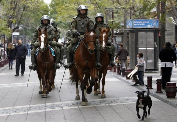 Un grupo de carabineros patrulla una calle hoy, miércoles 24 de agosto de 2011, durante la primera jornada de paro nacional de dos días convocado por la Central Unitaria de Trabajadores (CUT), en Santiago de Chile. Una normalidad relativa, perturbada por frecuentes enfrentamientos entre manifestantes y la policía, que han dejado al menos una docena de lesionados y varias decenas de detenidos, se ha podido observar en Chile este miércoles. EFE/Felipe Trueba