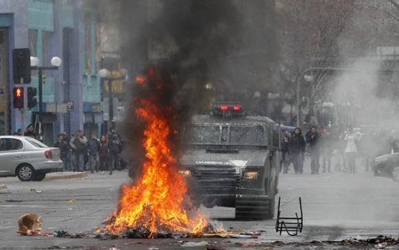 Un vehículo antidisturbios permanece frente a una barricada hoy, miércoles 24 de agosto de 2011, durante los altercados en el centro de Santiago de Chile, en la primera jornada de paro nacional de dos días convocado por la Central Unitaria de Trabajadores (CUT). Una normalidad relativa, perturbada por frecuentes enfrentamientos entre manifestantes y la policía, que han dejado al menos una docena de lesionados y varias decenas de detenidos, se ha podido observar en Chile este miércoles. EFE/Felipe Trueba