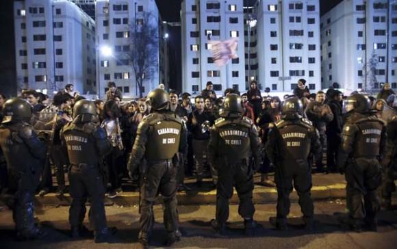 Varios carabineros vigilan a los miles de manifestantes que participan en una cacerolada anoche en Santiago en apoyo de los estudiantes que demandan una mejor educación pública. EFE/Felipe Trueba