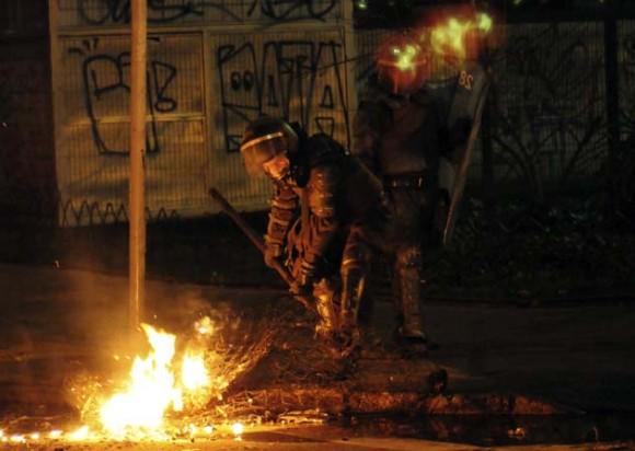 Carabineros limpian una barricada durante los disturbios tras la marcha de miles de estudiantes universitarios y de secundaria junto con otros sectores sociales, hoy, 9 de agosto de 2011, por el centro de Santiago de Chile durante las manifestaciones estudiantiles ocurridas en demanda de una educación de calidad y gratuita. EFE/Ariel Marinkovic