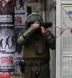 """Mientras un policía antimotines fotografía a manifestantes en Santiago, el ministro de Economía reconoció que si no tuviera dinero para pagar la educación de sus hijos """"también marcharía""""."""