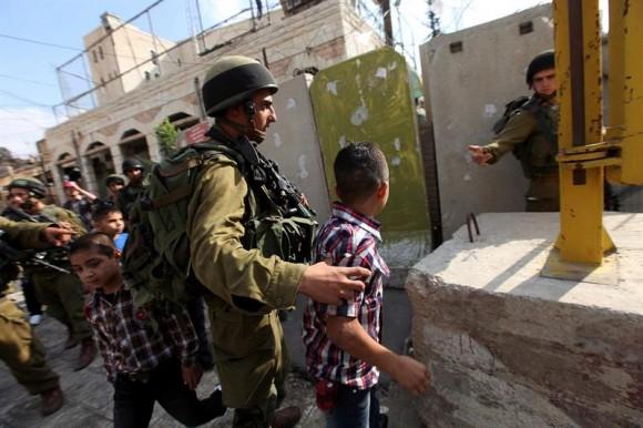 Soldados israelitas detienen a niños palestinos porque jugaban con armas de plástico. Foto: AP