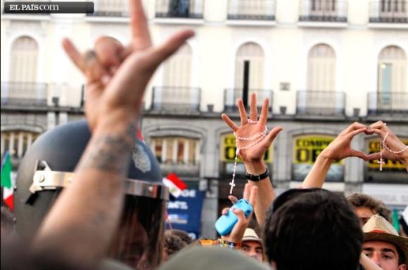 'Cuernos' y crucifijos. Manifestantes y peregrinos se intercambian gestos en la Puerta del Sol, en Madrid.Foto: Carlos Rosillo, El País.