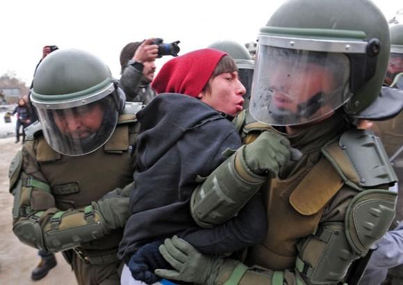 Un joven es golpeado y apresado por los carabineros en la manifestación del 4 de agosto.Foto: AFP