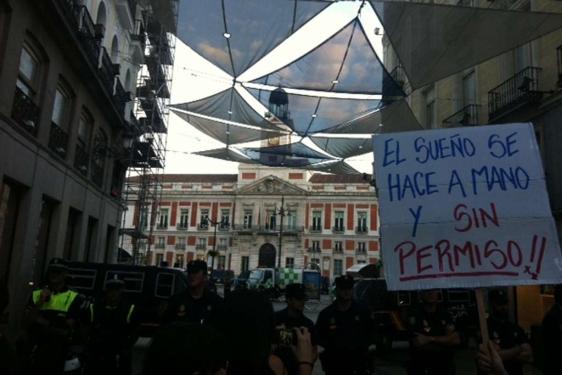 Una pancarta con versos de Silvio Rodríguez en manos de un manifestante, frente a la policía que cerca la Puerta del Sol en Madrid