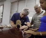 El lutier Jeffrey Bollblich, izquierda, repara un instrumento en la Escuela Nacional de Arte de Cuba en La Habana, Cuba, el miércoles 7 de septiembre del 2011. Jazz at Lincoln Center regresó a la isla del Caribe con instrumentos para ser donados a cuatro escuelas de música y un grupo de talentosos músicos y lutiers quienes impartirán talleres a estudiantes y también repararán sus instrumentos dañados durante una visita de una semana. (AP oto/Javier Galeano)