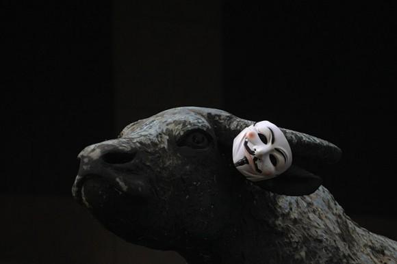 Una máscara de Guy Fawkes hizo popular por 'V de Vendetta' en la novela gráfica cuelga del cuerno de buey de bronce de una escultura fuera de la Bolsa de Hong Kong