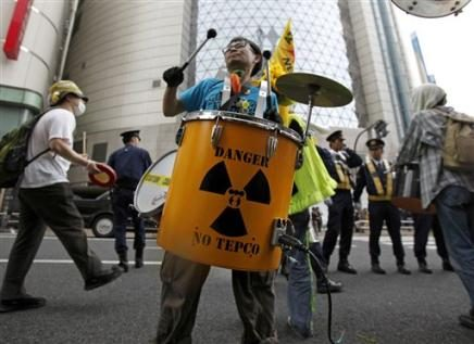 a-protester-beats-a-drum-in-front-of-a-showroom-of-tokyo-electric-power-co-tepco