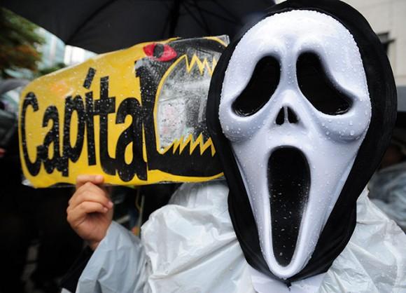 Un manifestante de Corea del Sur con una máscara sostiene una pancarta durante la manifestación Ocupar Seúl como parte de las protestas en todo el mundo