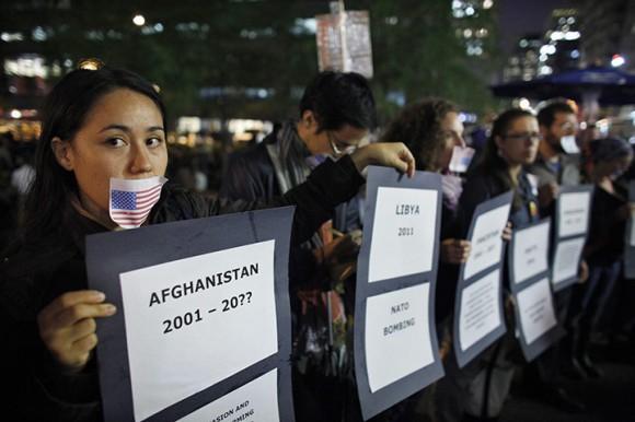 Manifestantes con una bandera de los EE.UU. pegada a la boca, sostienen carteles  en el Zuccotti Park, cerca de Wall Street en Nueva York. Foto: Reuters