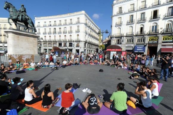 Un grupo de indignados practica yoga en la Puerta del Sol de Madrid en la mañana del 15 de octubre horas antes de las protestas. Foto: AFP