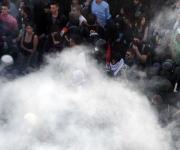 Manifestantes y policías italianos, entre una nube de humo en el centro de Roma. Foto: AFP